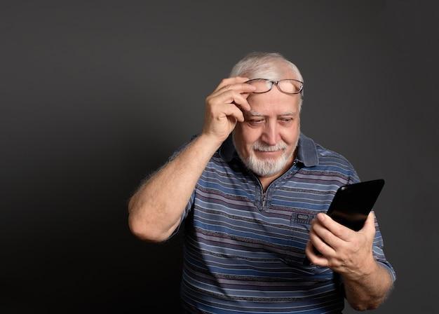 Bem-humorado homem sorridente segurando óculos e olhando para o tablet