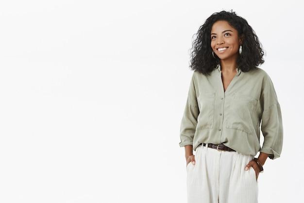 Bem-sucedida e bonita mulher afro-americana em pé com uma elegante camisa e calça hucky de mãos dadas nos bolsos