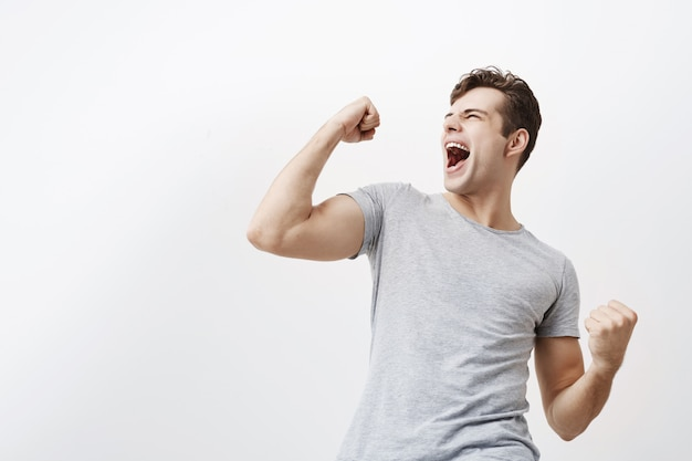 Bem sucedida emocional jovem desportista masculina caucasiana com cabelo escuro, gritando sim e levantando os punhos cerrados no ar, sentindo-se animado. pessoas, sucesso, triunfo, vitória, vitória e celebração.