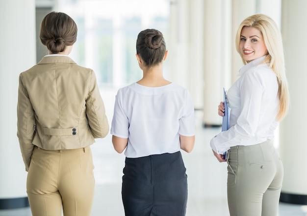 Bem sucedida equipe de senhoras de negócios, movendo-se juntos no escritório