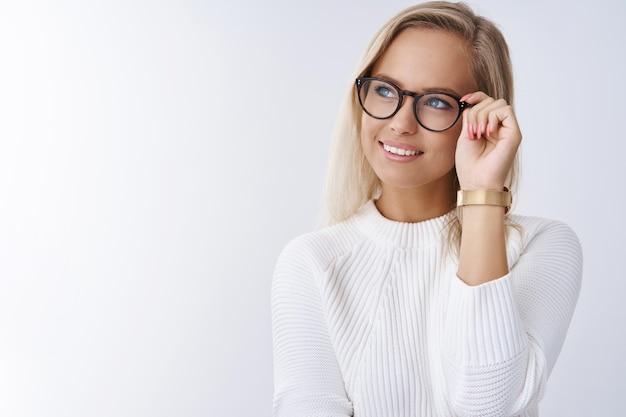 Bem-sucedida jovem elegante e elegante de óculos e suéter, parecendo encantada com um sorriso feliz e satisfeito no canto superior esquerdo, verificando óculos pensando ou sonhando acordado sobre a parede branca.