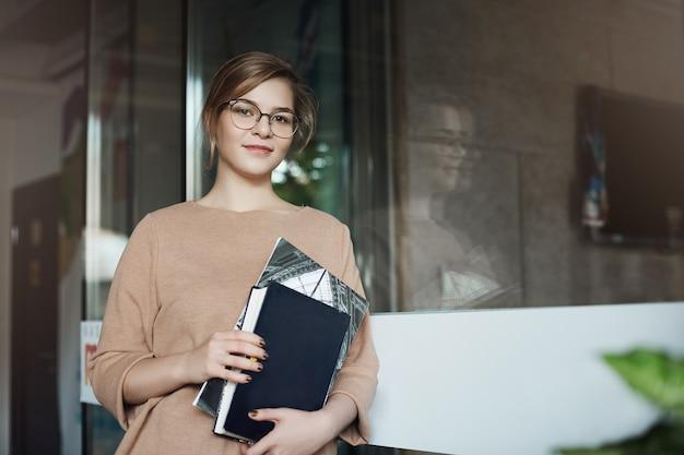 Bem sucedida jovem empresária andando pelo corredor no escritório, segurando livros, olhando com um leve sorriso.