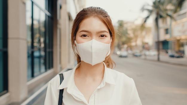 Bem sucedida jovem empresária asiática em roupas de escritório da moda, usando máscara médica e sorrindo na rua.