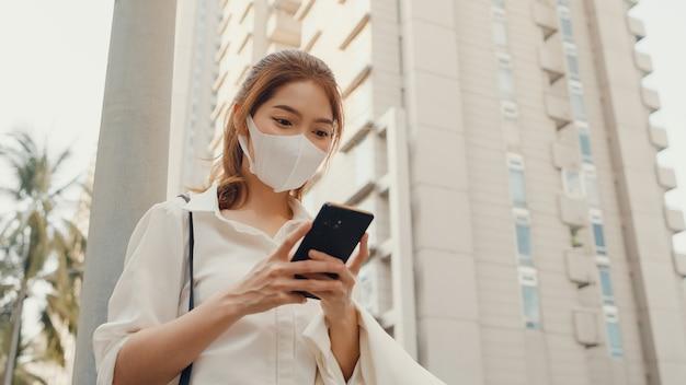 Bem-sucedida jovem empresária asiática em roupas de escritório da moda, usando máscara médica usando smartphone