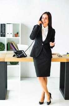 Bem sucedida jovem empresária em pé com a perna cruzada em frente a mesa falando no telefone