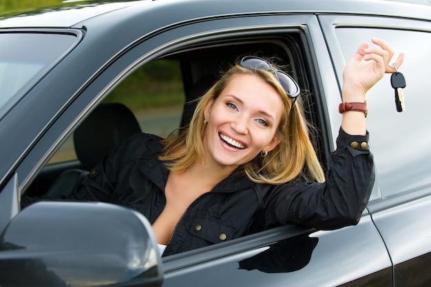 Bem-sucedida linda mulher feliz no novo carro com as chaves - ao ar livre