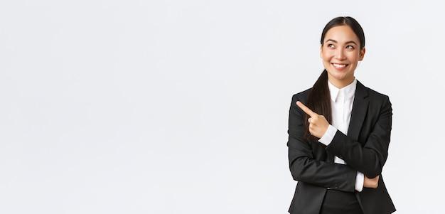 Bem-sucedida otimista sorridente gerente asiática feminina, empresária de terno, parecendo confiante e apontando o canto superior esquerdo com um sorriso satisfeito, com um fundo branco encantado
