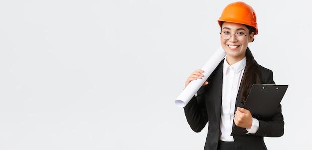 Bem sucedido arquiteto feminino asiático em terno de negócio e capacete segurando plantas e prancheta com ...