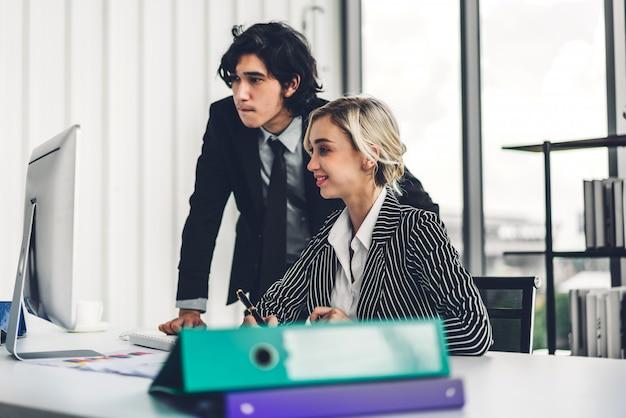 Bem sucedido de dois negócios casuais discutindo e trabalhando com computador desktop.