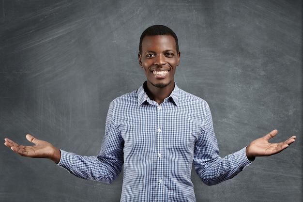 Bem sucedido empresário africano com sorriso feliz e confiante, vestido com camisa quadriculada azul, segurando suas mãos no gesto de boas-vindas