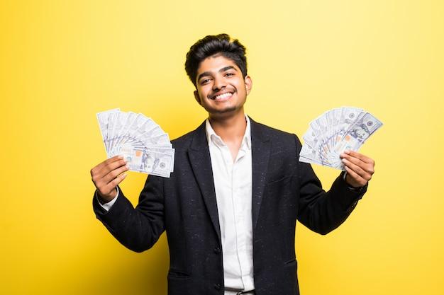 Bem sucedido empresário indiano com notas de dólar na mão terno clássico, olhando para a câmera com um sorriso em pé contra a parede amarela