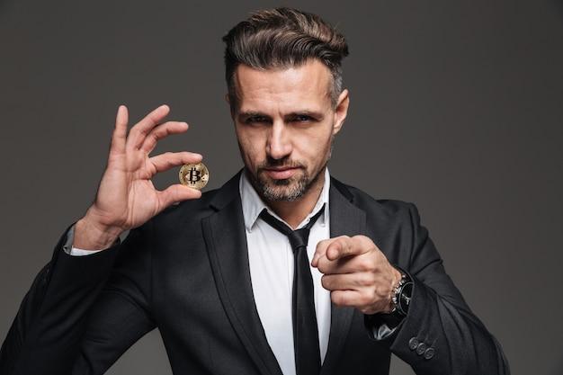 Bem sucedido empresário masculino de terno e gravata, segurando a moeda criptográfica e apontando o dedo na câmera, isolada sobre a parede cinza escura