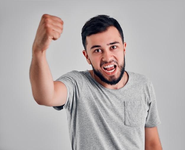 Bem sucedido esportista masculino caucasiano emocional jovem com cabelos escuros gritando sim e levantando os punhos cerrados no ar, sentindo-se animado. pessoas, sucesso, triunfo, vitória, vitória e celebração