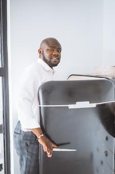 Bem sucedido jovem empresário afro-americano abre uma geladeira vintage em seu apartamento conce ...