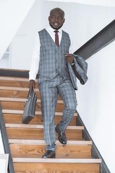 Bem sucedido jovem empresário afro-americano desce escadas para trabalhar no conceito de manhã de luxu ...