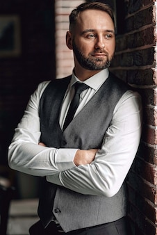 Bem sucedido jovem empresário de colete e gravata. com um corte de cabelo e barba com estilo