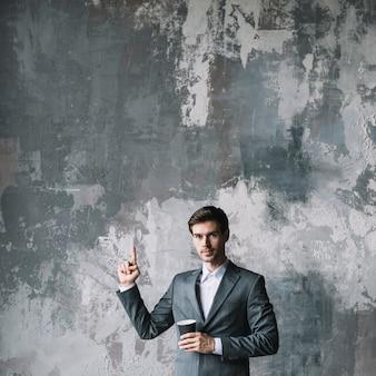 Bem sucedido jovem empresário de pé contra a parede de concreto, segurando a xícara de café, apontando o dedo para cima