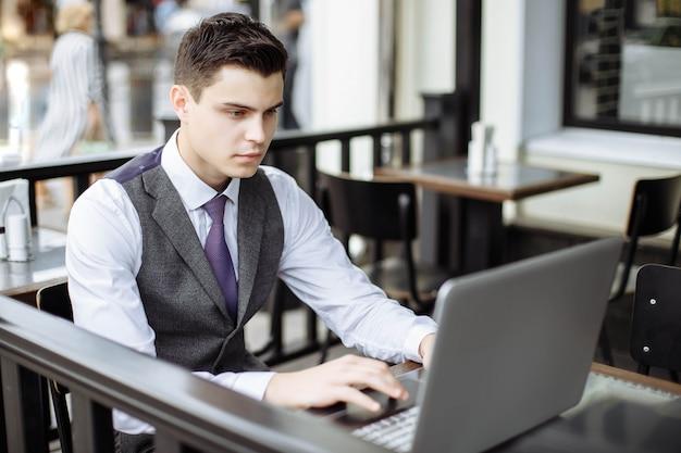Bem sucedido jovem empresário digitando no laptop no café