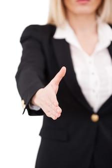 Bem-vindo a bordo! mulher de negócios confiante e madura estendendo a mão para apertar e sorrir em pé, isolado no branco