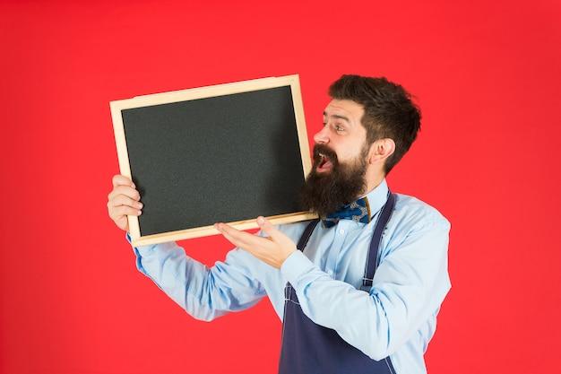 Bem-vindo a bordo. placa do menu. chef de homem feliz com quadro-negro, copie o espaço. receber. publicidade de restaurante ou café. hipster barbudo cozinheiro no avental. ótima cozinha. cozinhar por receita. bem-vindo ao time.