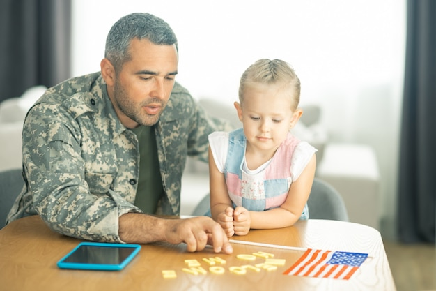 Bem-vindo a casa. filha amorosa e atraente recebendo o pai que serve nas forças armadas em casa