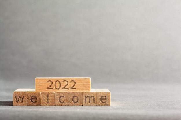 Bem-vindo a inscrição de 2022 gravada em blocos que seguram os dedos em um fundo cinza