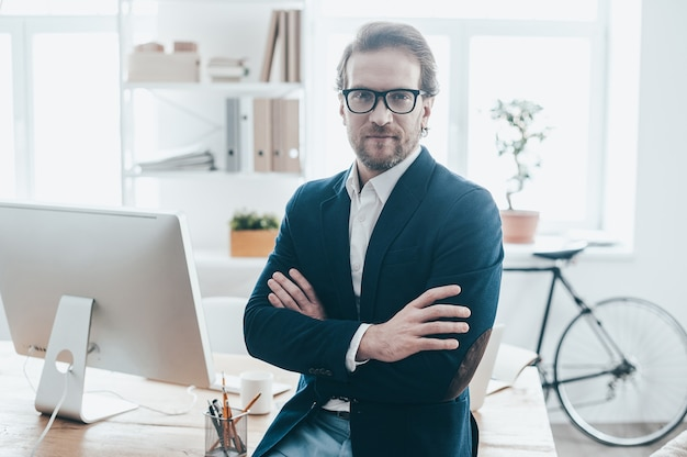 Bem-vindo ao meu escritório. jovem bonito usando óculos, com os braços cruzados e olhando para a câmera enquanto está sentado na mesa no escritório criativo Foto Premium