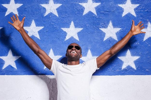 Bem-vindo aos eua! africano jovem feliz em óculos de sol, levantando os braços e sorrindo enquanto se apoiava na bandeira americana