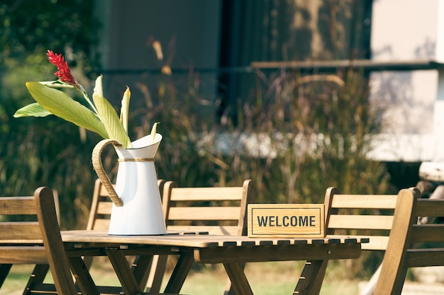 Bem-vindo sinal coloque em uma mesa de madeira com uma cadeira