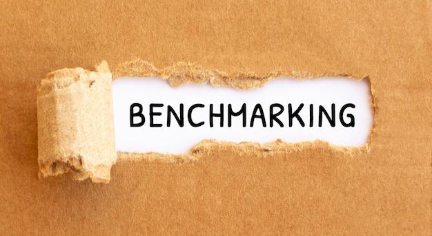 Benchmarking do texto aparecendo atrás do papel pardo rasgadocultura do texto aparecendo atrás do papel pardo rasgado.
