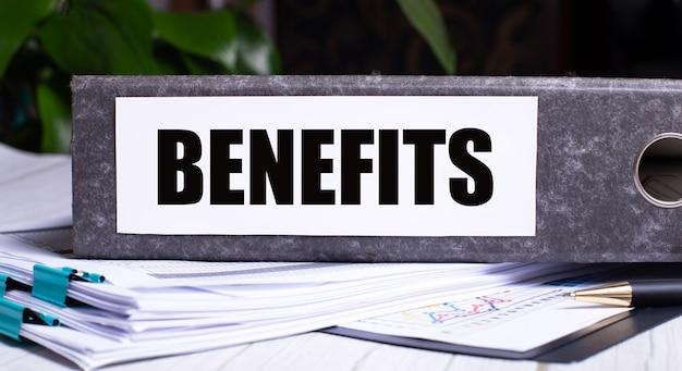 Benefícios está escrito em uma pasta cinza ao lado dos documentos. conceito de negócios