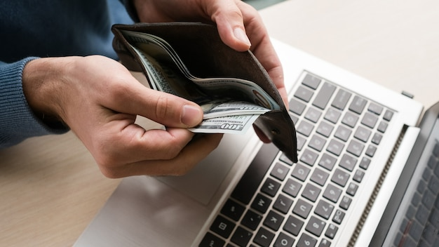 Benefícios financeiros de trabalhar em empresa de ti. homem segurando dinheiro, dólares. desenvolvimento de software de tecnologias de internet, aplicativos, conceito de programação