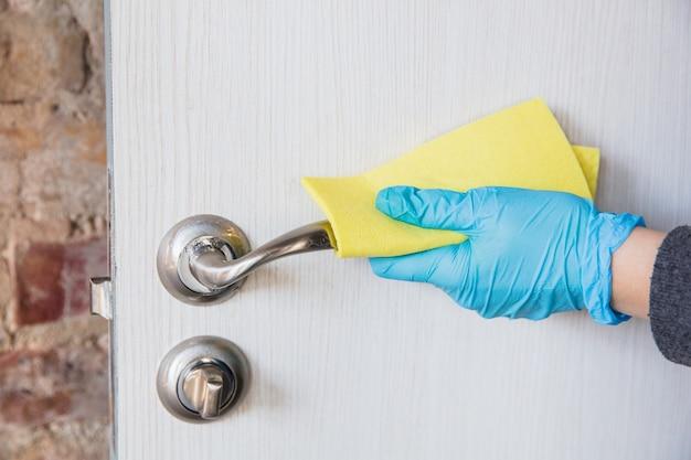 Bens essenciais durante a epidemia - prevenção e proteção da propagação do coronavírus covid-19. mão em luvas de desinfecção de superfícies com desinfetante em casa. limpeza contra o vírus da pneumonia.
