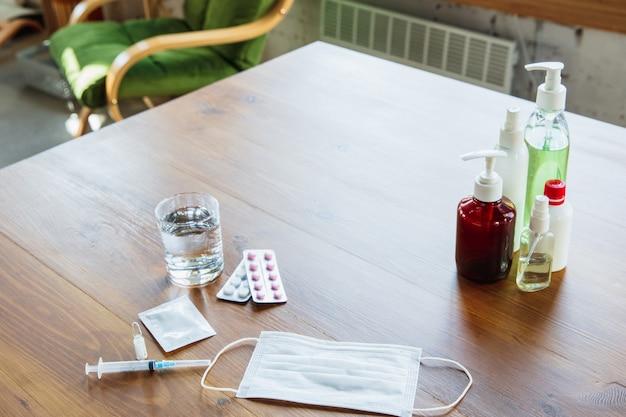 Bens essenciais durante a epidemia - prevenção e proteção da propagação do coronavírus. proteja o sistema respiratório contra a pneumonia, covid-19. desinfetantes, máscara facial, comprimidos na mesa de madeira.