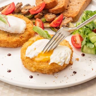 Bento ovos em um prato, um garfo rasga um ovo e a gema flui para fora.
