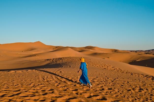 Berber de costas caminhando em direção às sombras de uma caravana de turistas montados em um camelo