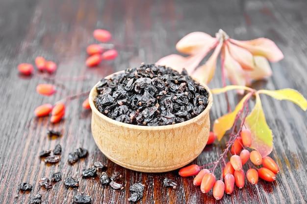 Bérberis pretos secos em uma tigela, raminhos com frutas frescas e folhas no fundo da placa de madeira