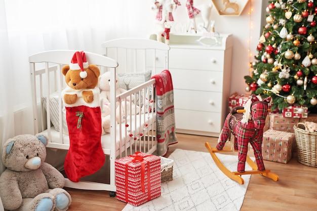 Berçário de natal, decoração de natal no quarto das crianças, sala de jogos infantil decorada para o ano novo, quarto das crianças brancas. brinquedos de natal e presentes no quarto das crianças, cama branca com brinquedos macios