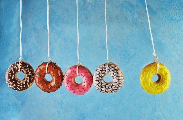 Berço de newton com donuts multicoloridos com glacê e granulado sobre fundo azul.