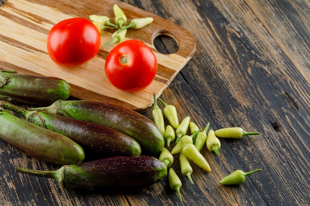 Beringelas com tomates, pimentas na placa de madeira e de corte, vista de alto ângulo.