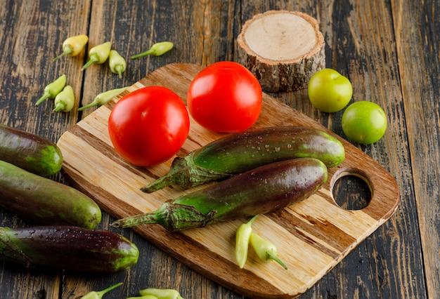 Beringelas com tomates, pimentos, ameixas verdes, madeira na tábua de madeira e corte, vista de alto ângulo.