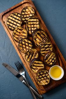 Beringelas vegetais fritas com óleo na placa de madeira