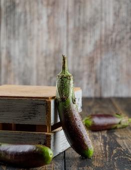 Beringelas verdes com vista lateral de caixa de madeira em um de madeira
