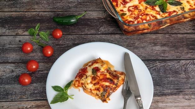 Berinjela à parmigiana um pedaço em um prato com garfo e faca ao lado da bandeja com cereja de berinjela