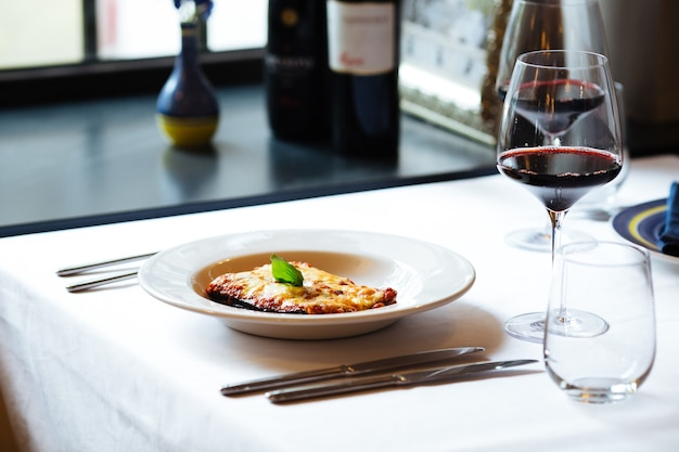 Berinjela à parmisã italiana com uma taça de vinho tinto