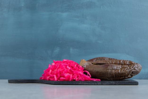 Berinjela apetitosa e repolho roxo em conserva na tábua de corte