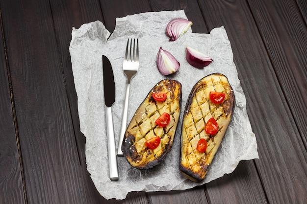 Berinjela assada com cebola e tomate, faca e garfo no papel. fundo de madeira escuro. vista do topo