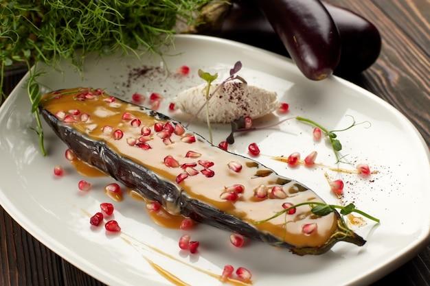 Berinjela assada com queijo e romã, num prato branco, na mesa de madeira