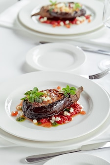 Berinjela assada pela metade com carne, queijo e tomate no fundo branco. pratos festivos para banquetes. menu de restaurante gourmet. fundo branco. Foto Premium