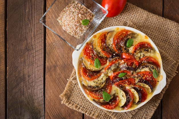 Berinjela crua de prato gratinado preparado com mussarela e tomate